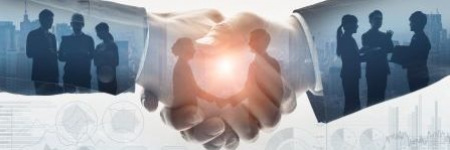 silhouette of shaking hands with business deals taking place within the hands