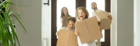 happy family carrying boxes into their new home