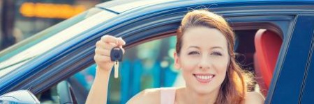 smiling lady in her new car holding up keys through an open car windo