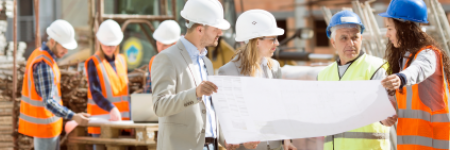 construction site with workers in hard hats reviewing blueprints