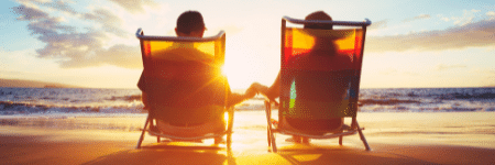 older couple holding hands sitting in beach chairs on the beach watching the sun set