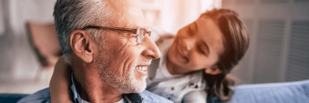 grandfather sitting on couch smiling at his granddaughter behind him