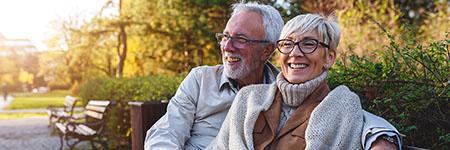 smiling senior couple sitting on a park bench enjoying long term care