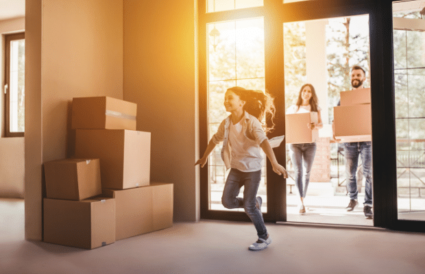 mom, dad, daughter running to move into their new house