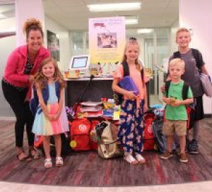 1ST SUMMIT BANK collects school supplies for kids showing 4 kids and bank employee surrounded by supplies